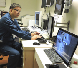 Fritz Cao, radiation therapist, at the SRT 100 console